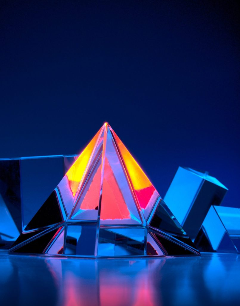 A shining glass pyramid in glowing pink yellow and orange is photographed on a blue backdrop